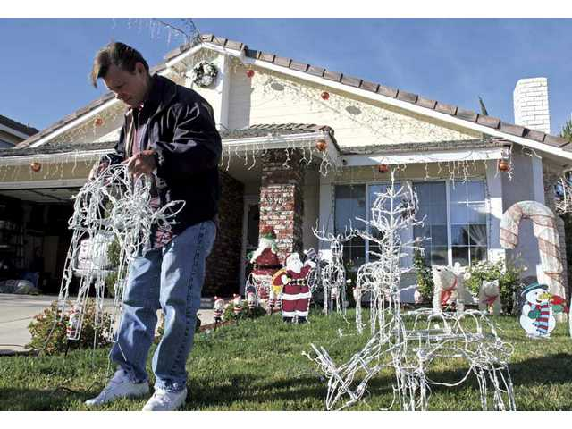 Wakefield Court resident Larry Anderson begins to pack up his Christmas decorations Monday. He and his neighbors have decorated their street together for the past eight years.