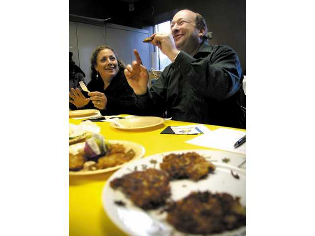 Rabbi Ira Rosenfeld judges one of the latke entries.