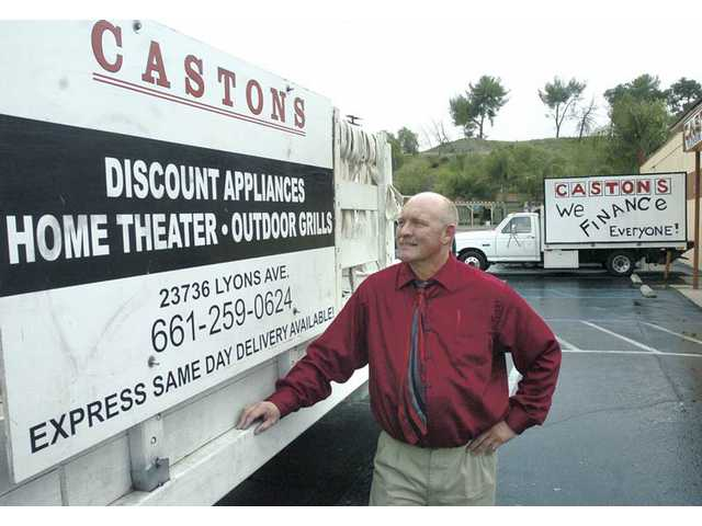 Rick Caston of Caston's TV & Appliances stands with his trucks in the parking lot of Caston's on Lyons Avenue in Newhall. The city has fined the landmark store for store signs that did not comply with its sign-restriction ordinance and for holding too many parking-lot sales.