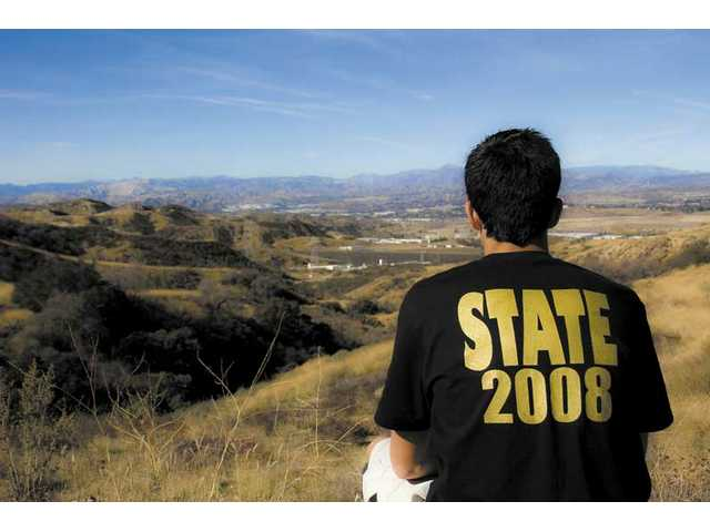 Golden Valley junior runner Seth Totten overlooks the mountains beyond the high school. Totten, who says he likes to unwind at this place, was fifth in the CIF State Division III Cross Country Championships.