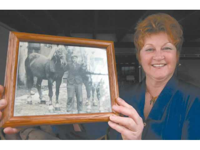 "Olga Kaczmar operates the DPcamps Web site, which helps families of ""Displaced Persons"" from World War II reunite. The site has become a clearinghouse for information on the DP camps. Kaczmar holds a cherished photograph in which her father cares for horses on a farm in Germany during the the war. He worked there as a slave laborer."
