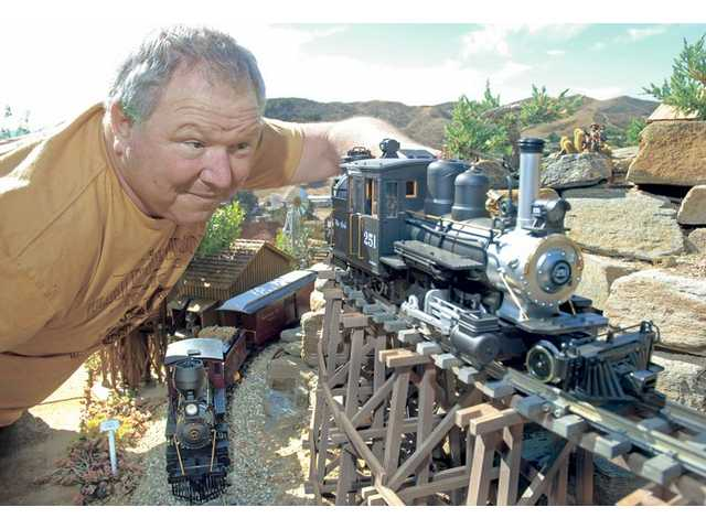 Dan Goetz, President of Ultra Violet Devices Inc. in Valencia watches two of his G-scale, narrow gauge electric engines travel over a section of the 600 feet of track that make up Dan and Debbie Goetz's Deadwood and Dry Gulch backyard Railroad. The 1:20 scale LGB Forney engine, on the track at right, costs $600 and the Mogul engine below left, is $400. The train's rail cars can cost from $25 to $100 each. Dan Goetz got wife Debbie interested in model railroading when they married 31 years ago, and they expanded their hobby to the 120 by 25 foot back yard layout when they moved to their Castaic home in 1992. The couple are members of the SCV Garden Railroad Club.