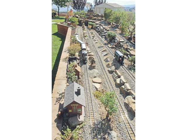 Dan Goetz works on one piece of the some 600 feet of track that sprawl across his backyard at his Castaic home.
