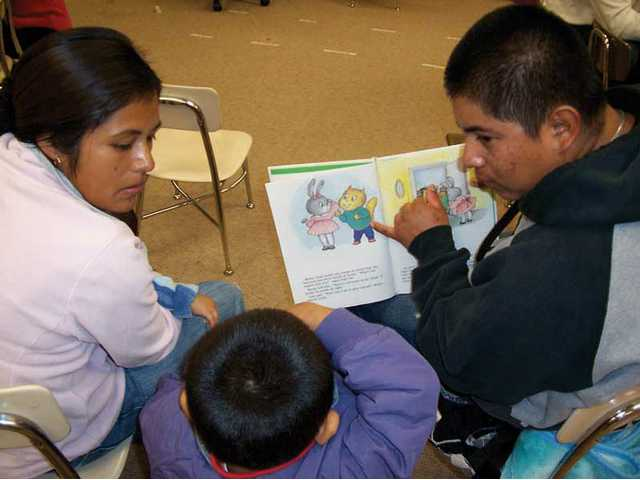 Preschooler Jesus Martinez reads with his mother, Marcelina De Santiago and his father, Emmanuel Martinez during family reading night Thursday at Canyon Springs Elementary School.