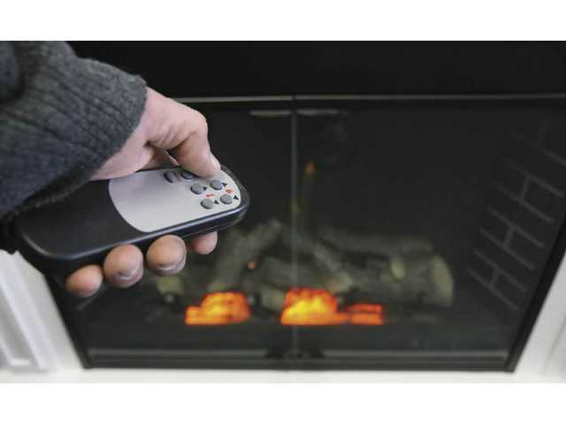 George Gharabghi adjusts an electric fireplace by remote control.