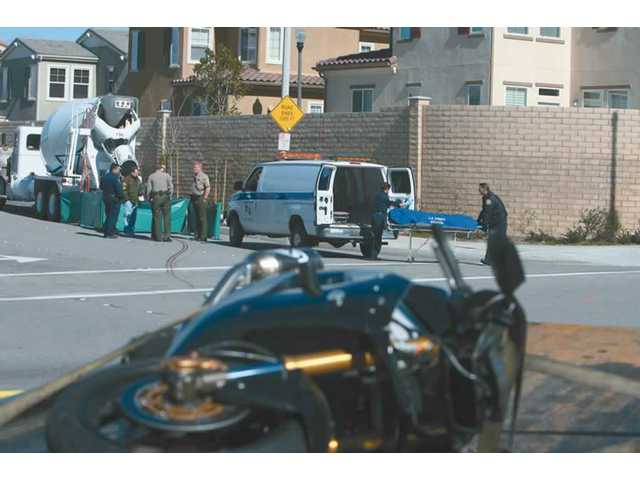 The motorcycle of a 25-year-old man lays in the foreground as Coroner's officials load his body into a van in the background Monday afternoon in Canyon Country. Sheriff's deputies survey the scene in the background, as well.