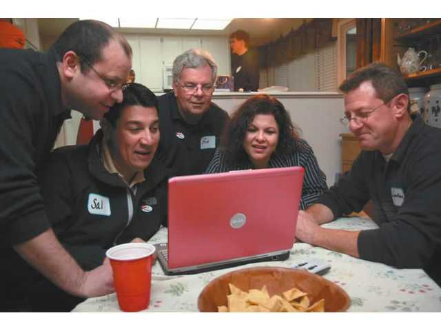 Members of the Democratic Club of Santa Clarita Valley watch election results on a laptop on Tuesday evening. From left are Michael Cruz, Sal Ramirez, Bill Bailey, Linda Valdes, and president of the club Jonathan Kraut.