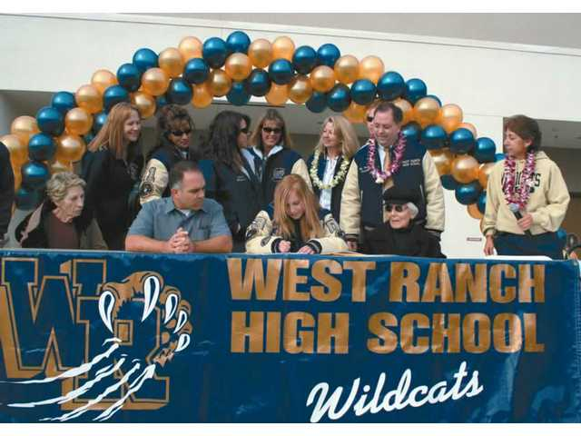 With family and school administrators surrounding her, West Ranch High soccer player Gina Tumasone, bottom row third from right, signs a letter of intent Wednesday to accept an athletic scholarship from the University of Hawaii-Hilo.