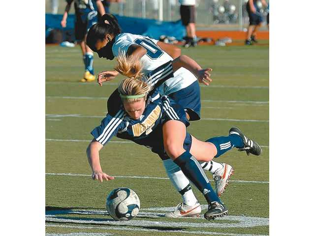 West Ranch's Camille Kirkpatrick, bottom,  battles for the ball as she collides with Saugus' Nicole Penick Thursday.