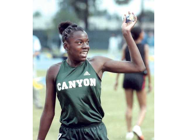 Canyon's Alysia Johnson waves after qualifying for  the state meet in the 400 at the CIF Masters Meet on May 25 at Cerritos College.