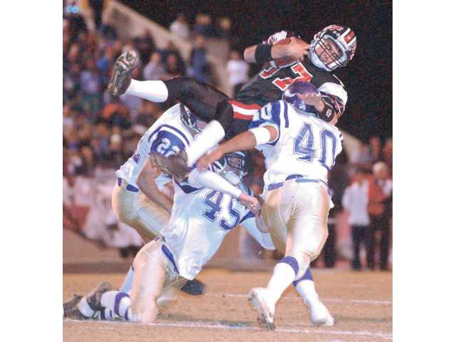 Hart quarterback Matt Moore (17) goes airborne over Valencia's Matt Lien (22), Mark Munos (45) and Danny Pina (40) during the CIF-Southern Section Division III title game on Dec. 7, 2001.