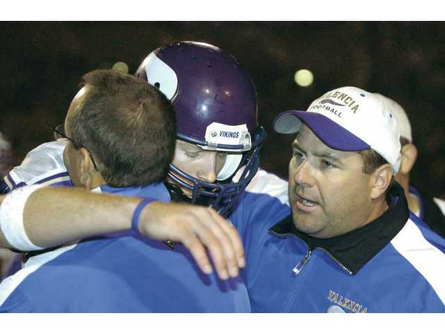 Valencia quarterback Michael Herrick, center, is embraced by his two head coaches from Valencia, Brian Stiman, left, and Larry Muir, right, after breaking the state's all-time passing yardage record on Nov. 11, 2005.