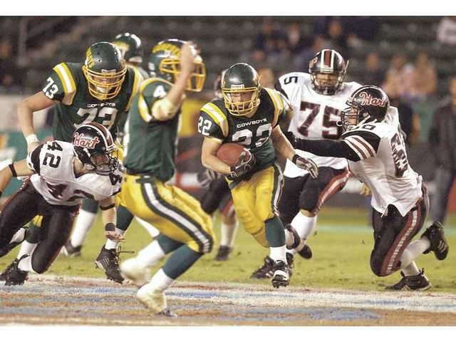 Canyon's Christopher Kingsbury (22) rushes past Hart defenders during the Cowboys' 21-13 victory over Hart in the CIF-Southern Section Division II championship on Dec. 9, 2005. It was the Cowboys' first CIF title since 1985.