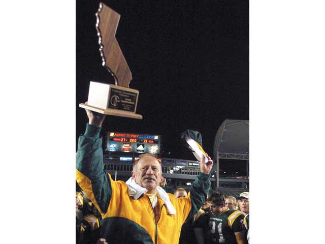 Canyon football head coach Harry Welch hoists his team's 2006 state-championship trophy over his head.