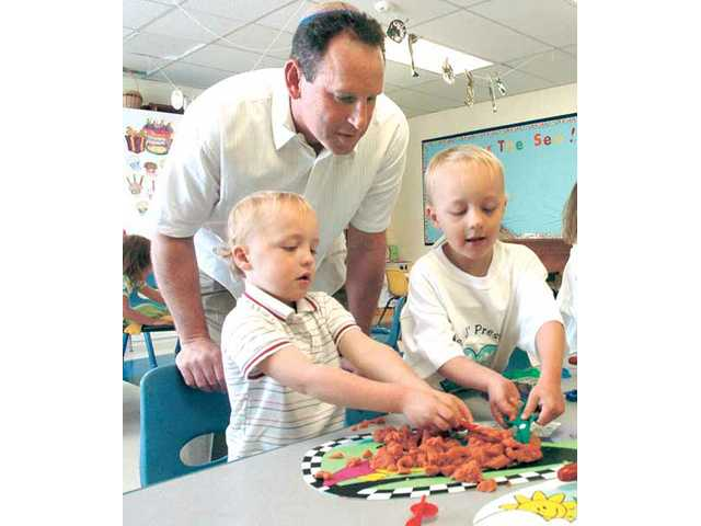 Rabbi Mark Blazer visits the Temple Beth Ami preschool as twins Jack and Isaac Slabich, 3, play with Play Doh.