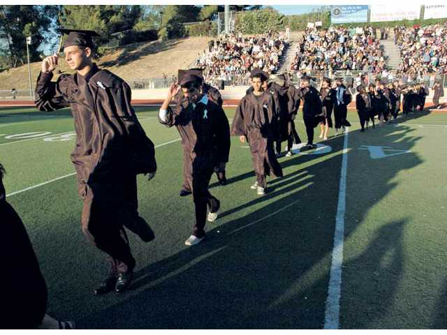 Golden Valley's graduating seniors hold on to their caps during their windy graduation ceremony Friday at College of the Canyons' Cougar Stadium. For the full story, see Sunday's edition.