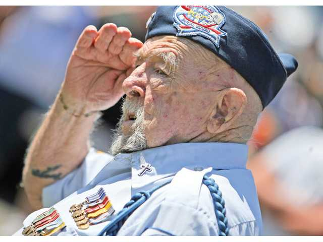 Sylmar resident Jim Tukesbrey, Chaplain for the All Veterans Burial Squad, and United States Army Air Corps veteran, salutes the American flag.