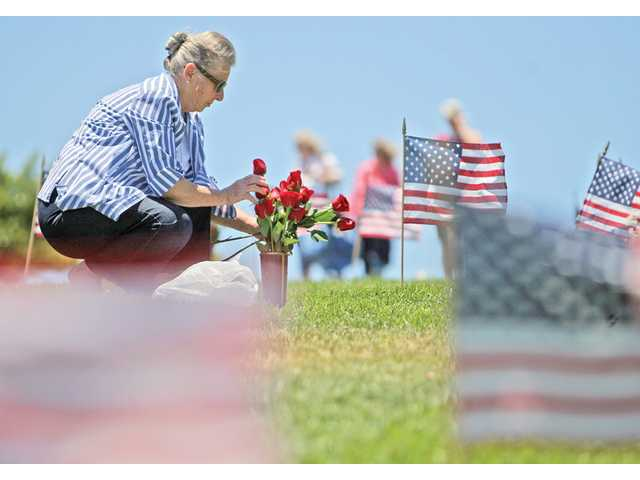 Anne Coleman, of Oxnard, pays tribute to her late husband, and Army veteran of the Korean War, Delmar Coleman, at Eternal Valley Memorial Park and Mortuary on Monday.