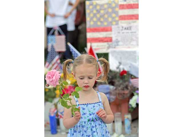 With a rose in hand, two-year-old Lacie Jelin of Stevenson Ranch attends the candlelight vigil for Marine Corps Pfc. Jake William Suter, who was killed in Afghanistan on Saturday, May 29, 2010.