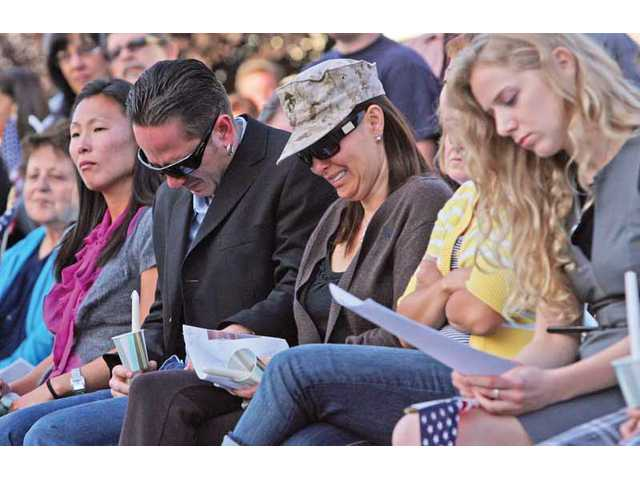 The death of Marine Corps Pfc. Jake William Suter is mourned by his stepfather, Chris, and mother, Michelle Unthank, at a candlelight vigil held outside their Stevenson Ranch home Wednesday.