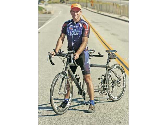Race Across America participant Tim Skipper stands with his Calfee tandem bike on The Old Road near his home in Castaic. Skipper will start the race on Saturday.