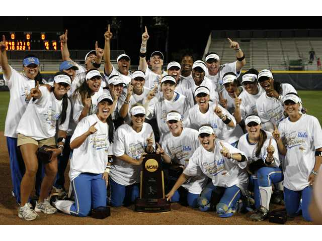 UCLA players gather around the trophy after a 15-9 win over Arizona gave them the NCAA Softball World Series championship on Tuesday in Oklahoma City. Hart graduates Destiny Rodino and Devon Lindvall both earned titles in their first collegiate seasons.