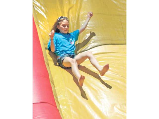 Natalie Hornbrook, 12, takes a plunge down one of two inflatable slides that were provided for the Bouquet Canyon Elementary's end-of-the-year celebration on Saturday.