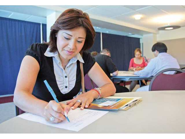 Yesenia Garcia of Canyon Country fills out an application to Insurance and Financial Services, at the job fair sponsored by the Santa Clarita WorkSource Center in the College of the Canyons University Center on Friday morning.