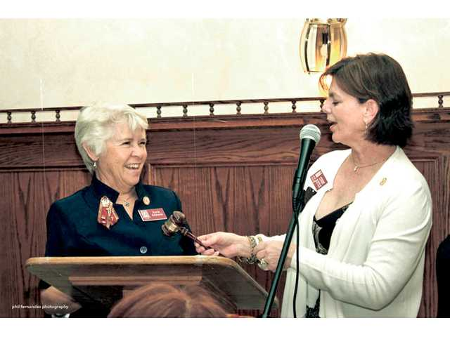 New Zonta President Karla Edwards is passed the gavel by outgoing President Cindy Kittle.
