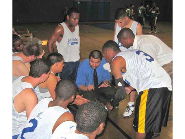 Bowman High club basketball coach Jose Rosales works on strategy with his players during a timeout. Rosales and teacher Nate James recently completed their first season as coaches of the school's first basketball team. Their efforts were assisted by the local chapter Boys & Girls Club. The Bowman Bulldogs finished their season 4-4.