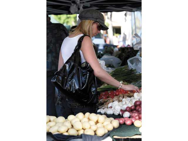Jenn Douglas, of Valencia, checks out the produce at the Newhall Farmer's Market, which is held Thursdays.