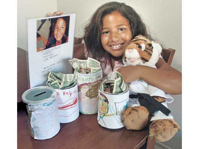 Shawn Dettenmier, 7, with some of the 16 cans she decorated in order to collect money to help out the Childrens Hospital Los Angeles. To date, she has collected approximately $700 to help the cause.