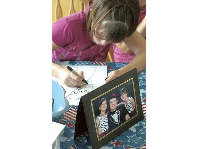 Eleven-year-old Jessica Howard draws while at the kitchen table of her family's Valencia home next to a picture of herself, her twin sister, Victoria, and her father, Tim, at a father-daughter school dance.