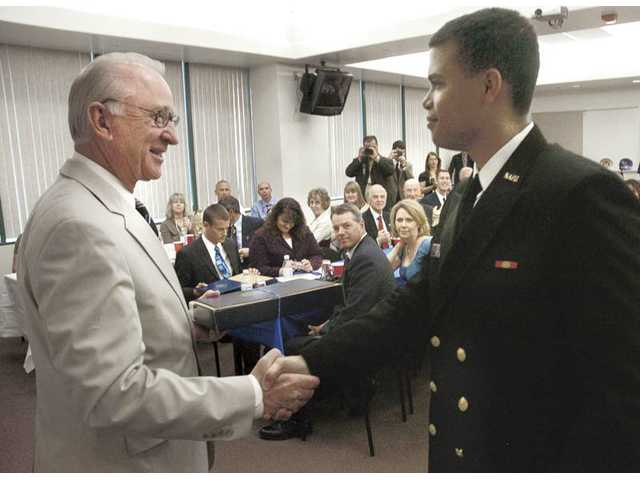 "Congressman Howard ""Buck"" McKeon, R-Santa Clarita, left, shakes hands with United States Naval Academy appointee Justin Shelton at a service academy recognition luncheon held in the Century Room at Santa Clarita City Hall on Saturday."