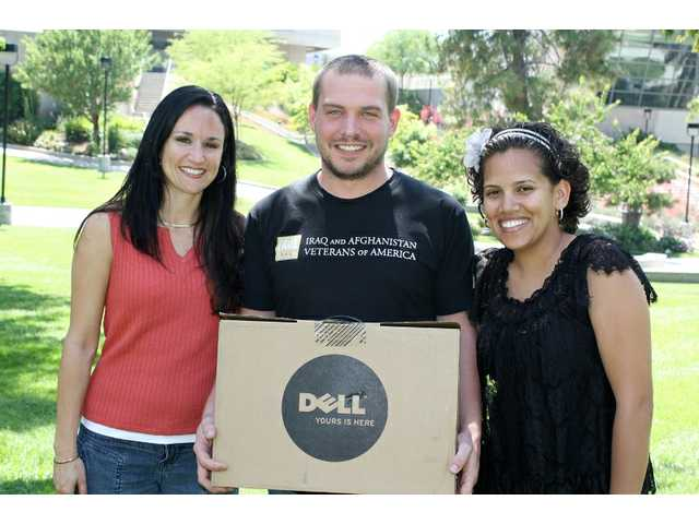 "College of the Canyons employees Wendy Trujillo and Celina Baguiao present Mike Hoder his new Dell laptop, top prize in the college's ""40 Ways to Change Your Life"" contest."