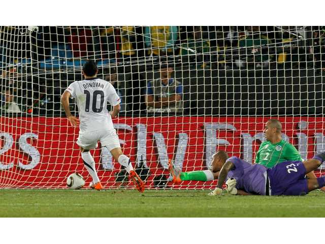 United States' Landon Donovan, left, scores a goal past Algeria goalkeeper Rais M'Bolhi, front right, and Algeria's Madjid Bougherra, back right, during the World Cup group C soccer match between the United States and Algeria at the Loftus Versfeld Stadium in Pretoria, South Africa, Wednesday, June 23, 2010.