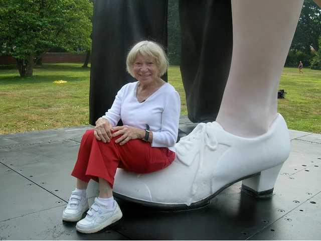 Edith Shain sits on the base of a monumental statue located in San Diego. She died on Sunday, June 20.