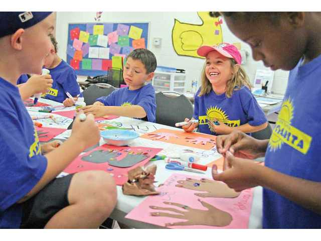 "Campers at Camp Clarita decorate their ""Hollywood Handprints"" made during the camp's arts-and-crafts time Monday morning."