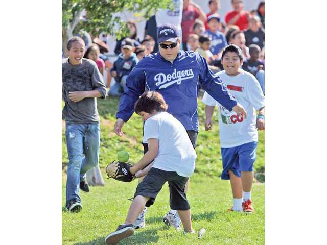 Sixth-grader Marco Gallegos attempts to tag out fourth-grade teacher Joseph Soqui out at home plate during the school's annual end-of-the-year Teacher Versus Sixth-Grade Class softball game played at McGrath Elementary School on Monday morning. The teachers' team defeated the students 10-6.