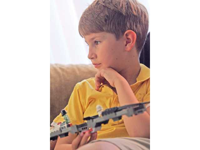 Jem Miller has a pensive moment with the Lego spaceship he crafted by himself without any instructions. Miller said he would like to be a rocket scientist someday. He starts second grade in the fall and is currently learning the difference between a belief and an opinion, as well as how to empathize with others.