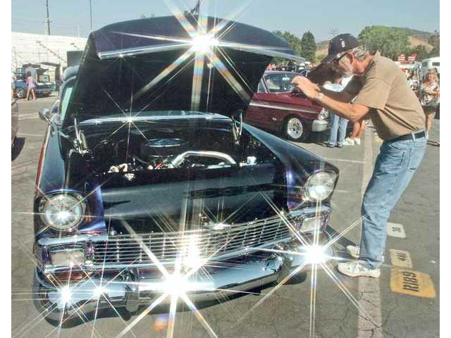 The reflections on the chrome of a classic 1950s Chevrolet Bel Air are enhanced by a star-effect lens filter as Joe Laslo, of San Fernando, takes a picture of its engine Saturday.