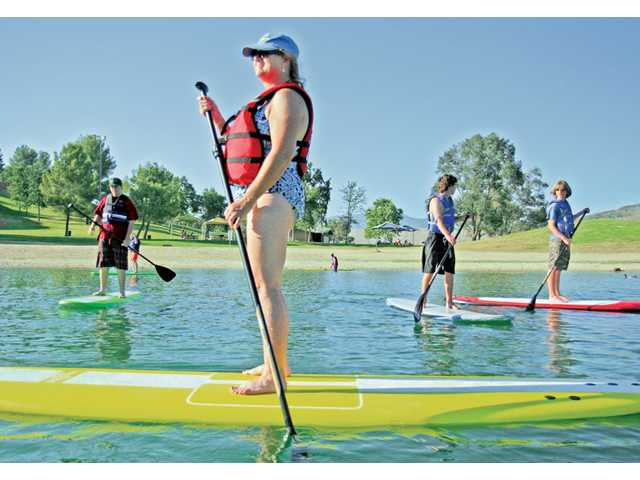 Valencia resident Julie Calane, front, and others stand-up paddle board around Paradise Cove at Castaic Lake on Wednesday evening. Classes are offered at the lake on Wednesday evenings from 5:30-6:30 p.m. and twice on Saturday mornings from 8-9 a.m. and 9:15-10:15 a.m.