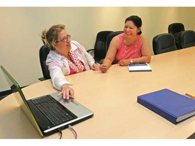 Bookkeeper Lois Lewis, left, of Double L Financial, meets with client Kelly Clark in the conference room of Barrister's Turnberry Lane location.
