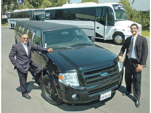 Kuldip Bali, left, and Vin Bali stand next to Lightning Limos' stretch Ford Expedition, one of the three-year-old company's 11 limos, Wednesday at the company's Valencia offices. Lightning's 35-passenger and 50-passenger party buses can be seen in the background.