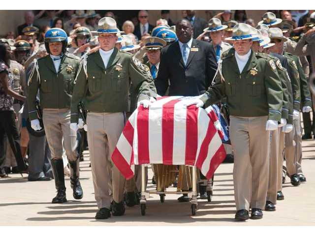 Pallbearers guide the casket of fallen California Highway Patrol Officer Philip Ortiz out of the Cathedral of Our Lady of the Angels following a funeral on Wednesday. Ortiz, one of five CHP officers killed on the job since May, was killed after he was hit by a car while writing a ticket.