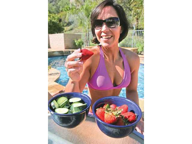 Rachel Cosgrove snacks on healthy cucumbers and strawberries as part of her strategy to look good in a bathing suit.