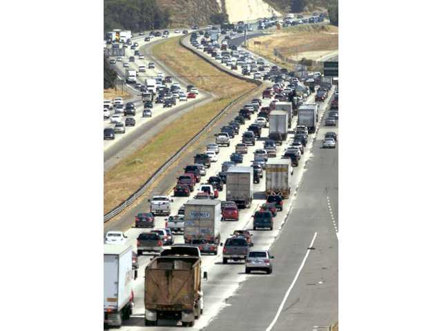 Looking southbound, traffic begins to pile up on Interstate 5 heading in both directions on Friday near the Lyons Avenue off-ramp. The Automobile Club is expecting a 19-percent increase in traffic over Fourth of July weekend.