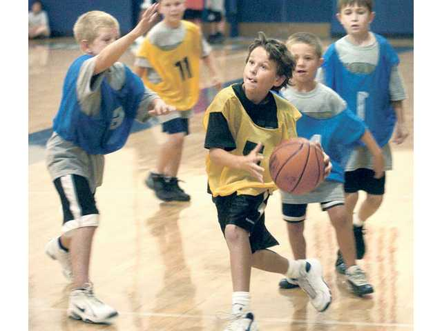 Ryan Prero, 10, center, drives under the basket as his team competes against three other teams made up of 73 participants ages 7-14 at the Master's 2010 Men's Basketball Camp at The Master's College on Tuesday.