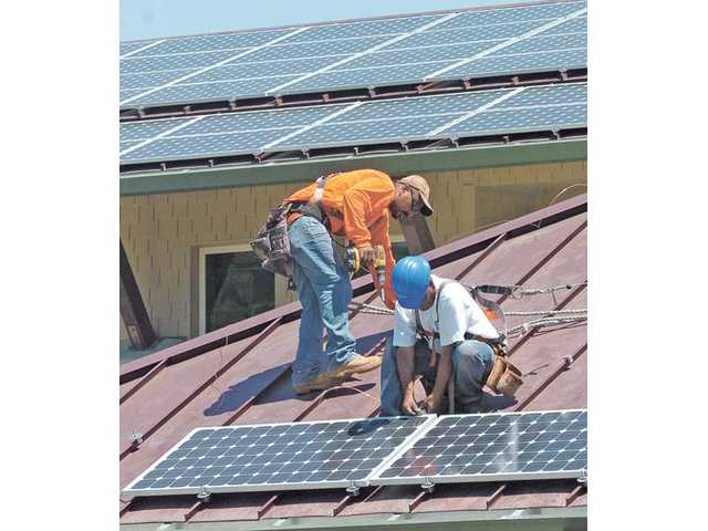 Workers install some of 202 the solar panels on the roof of the new Newhall County Water District Administration building in Newhall on Thursday.  The solar panels incorporated into the building's roof line will supply more than 50 percent of the office building's energy needs.