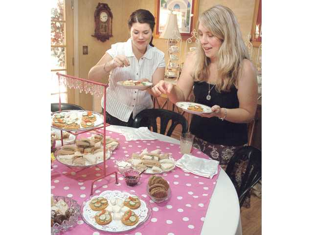 Guests Heather Ashor, left, and Stacy Koscheski sample Graham's treats at the tea.